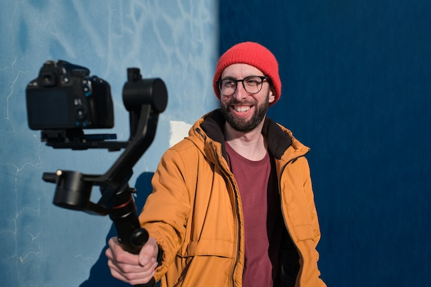 Videographer recording himself with a dslr camera on a motorized gimbal