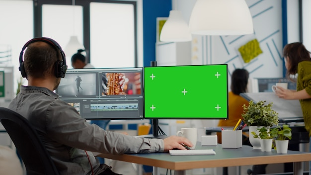 Videographer using computer with chroma key mock up isolated display editing video and audio footage...