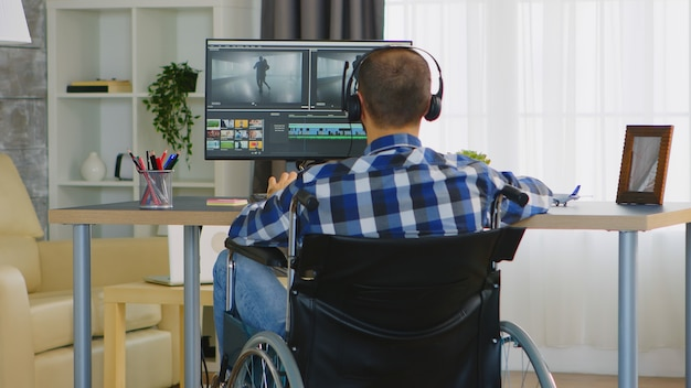 Videographer with handicap sitting on wheelchair doing color grading on film. wearing headphones.