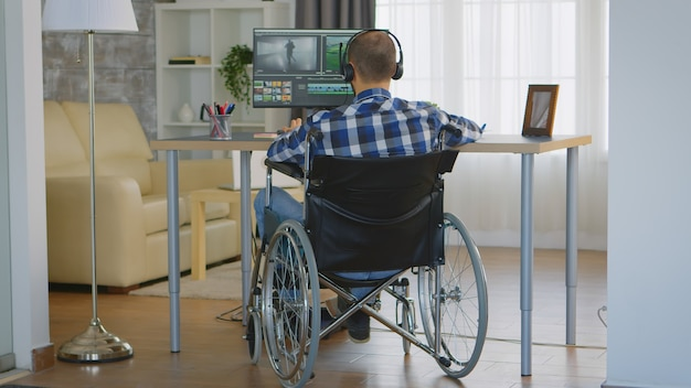 Videographer with headphones and moving handicap sitting on wheelchair working on movie.