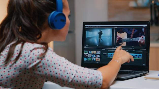 自宅からラップトップで作業し、夜にビデオとオーディオの映像を編集するビデオグラファー。プロフェッショナルデバイスの最新技術ネットワークワイヤレス処理フィルムモンタージュを使用する女性コンテンツクリエーター。