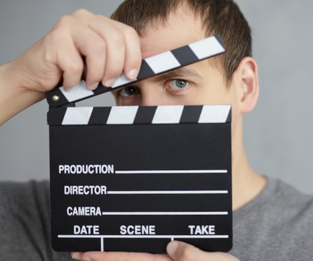Концепция видеосъемки и кинопроизводства - молодой человек закрывает лицо хлопушкой