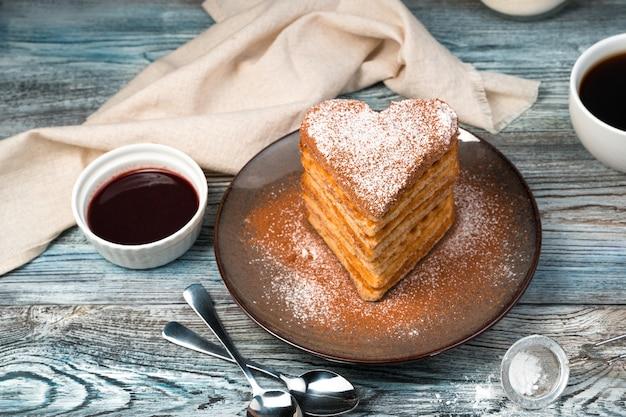Венские вафли в форме сердца с сахарной пудрой, ванилью и какао на деревянном сером фоне.