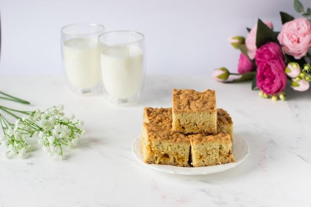 ミルクと花の表面に対して白いテーブルの上のウィーンのパイ