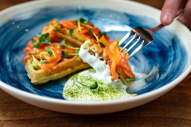 Viennese waffle with salmon and white sauce on a blue plate is eaten with a knife and fork. serving breakfast in a cafe and restaurant. serving the table and serving dishes for the banquet.