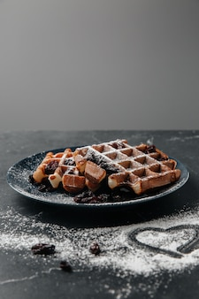 Viennese waffles, sprinkled with powdered sugar, on a dark textured table
