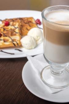 나무 테이블에 라떼 커피와 함께 비엔나 와플. 어떤 목적을 위해.