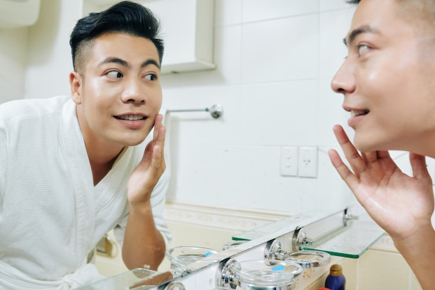 Vietnaemse man applying moisturizing lotion