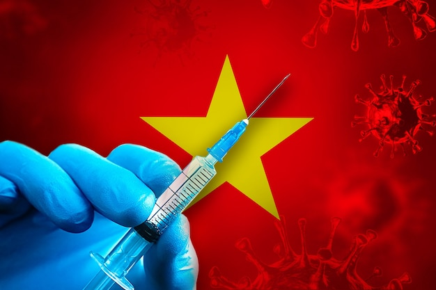 Vietnam covid19 vaccination campaign hand in a blue rubber glove holds syringe in front of flag