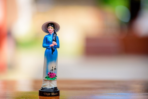 Vietnam doll souvenir on wooden table with blurred background.