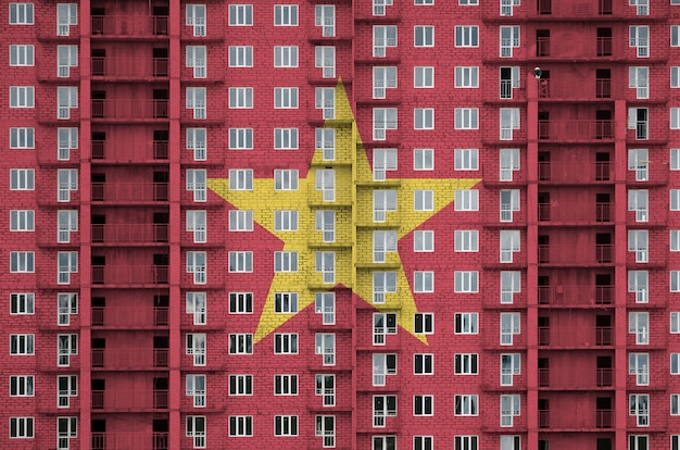 Vietnam flag depicted in paint colors on multi-storey residencial building under construction.