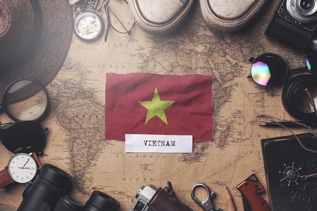 Vietnam flag between traveler's accessories on old vintage map. overhead shot