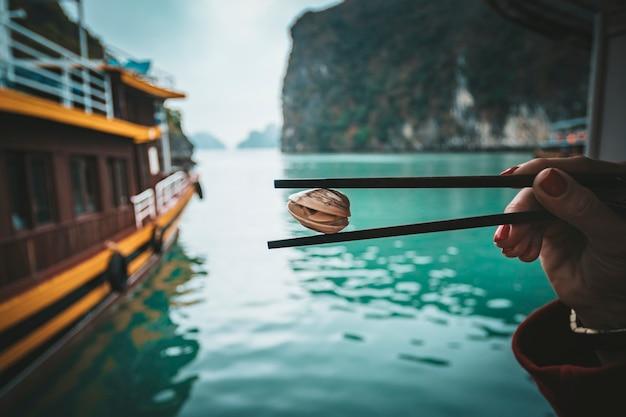 女性の手の棒にスパイシーなシーフードソースをかけたベトナム産グリーンムール貝。
