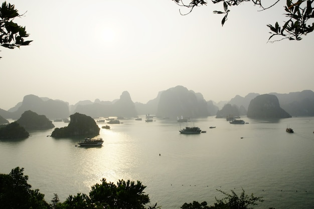 Vietnamese bay with boats plying the sea between mountains and rocks at sunset