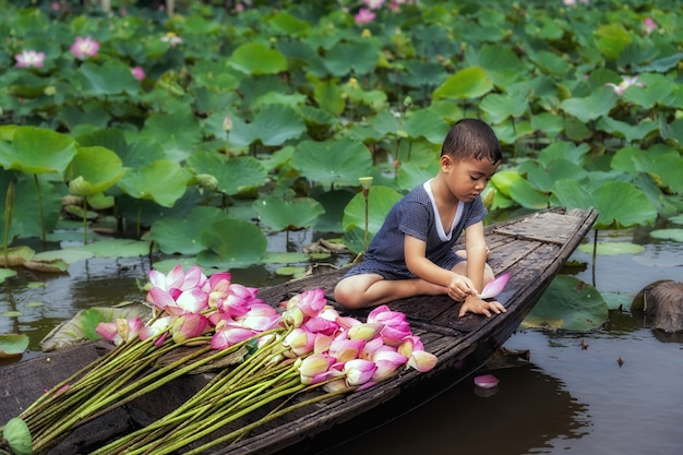 Vietnamese boy playing with pink lotus leaf when his mom boating the traditional wooden