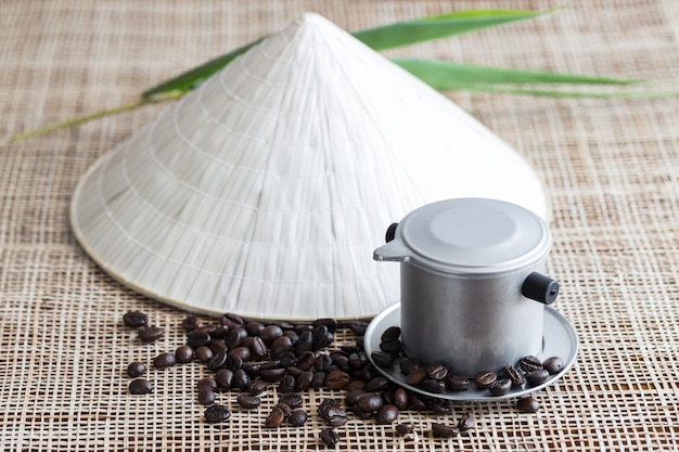 Vietnamese coffee brewing pot with coffee beans