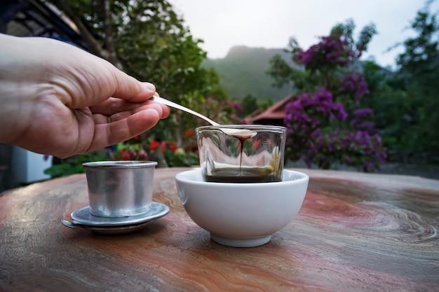 Вьетнамский кофе на столе на фоне красивой вьетнамской природы в уличном кафе. мужчина размешивает кофе ложкой. чайная ложка в руке.