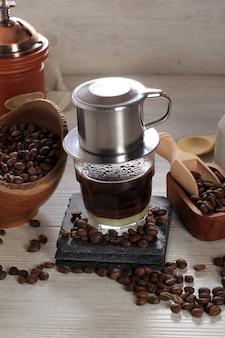 유리 컵에 연유를 넣은 베트남 커피와 전통 금속 커피 메이커 핀. 베트남 커피 드립을 만드는 전통적인 방법. 텍스트를 위한 공간입니다. 또는 광고