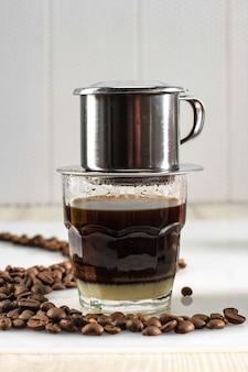 Вьетнамский кофе со сгущенкой в стеклянных чашках и традиционная металлическая кофеварка phin. традиционный способ приготовления вьетнамской кофейной капли. место для текста или рекламы