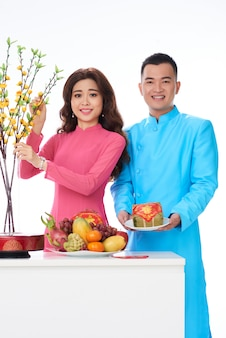 Vietnamese couple in bright traditional clothes posing in studio with fruit and flowers