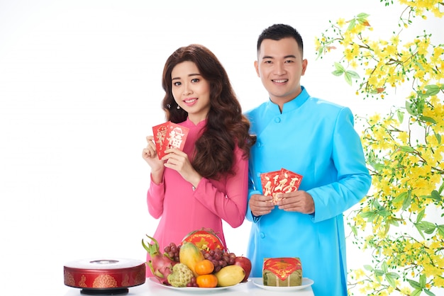 Vietnamese couple posing in studio with blooming mimosa and traditional new year attributes