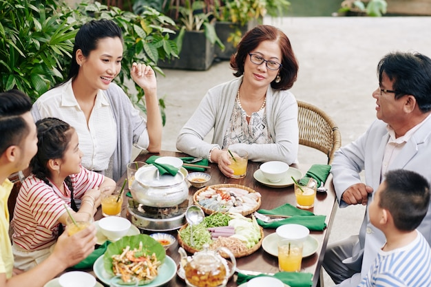 Vietnamese family enjoying tasty dishes and good conversation at lunar new year celebration