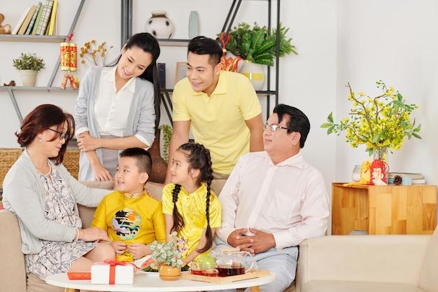 Вьетнамская семья собралась дома, чтобы отпраздновать лунный новый год и пожелать удачи маленьким детям в традиционных костюмах.