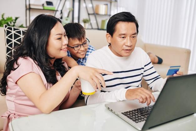 ブラックフライデーにオンラインで購入するためにラップトップに集まったベトナム人家族
