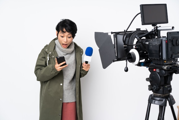 Vietnamese female reporter holding a microphone and reporting news surprised and sending a message