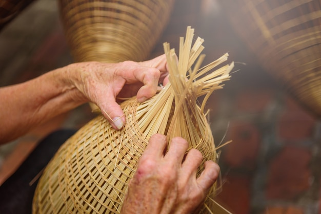 Vietnamese fishermen are doing basketry for fishing equipment at morning in thu sy village