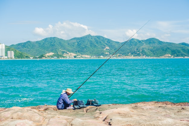 Vietnamese fishermen sitting on the edge of a cliff and fishing.