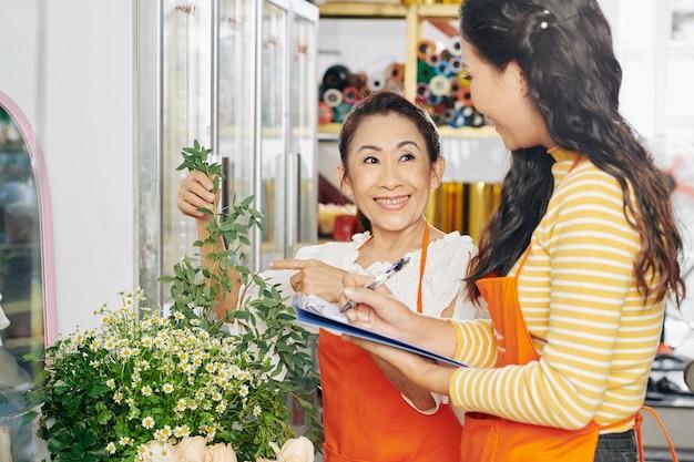 베트남 플로리스트와 그녀의 조수가 식물을 관리하고 문서에 메모하는 방법을 논의