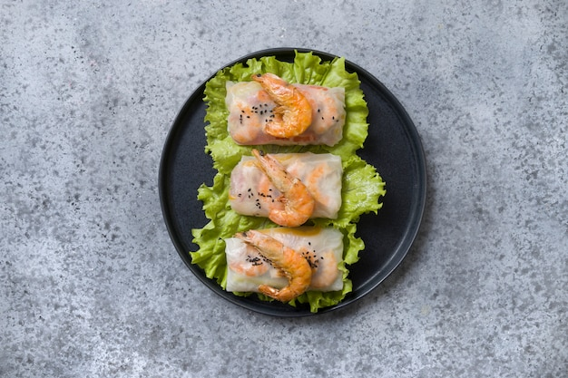 Vietnamese food spring rolls with shrimps in rice paper on grey. view from above. asian cuisine.