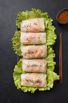 ベトナム料理の春巻き野菜、黒い石の背景にライスペーパーのエビ。上からの眺め。アジア料理。垂直フォーマット。