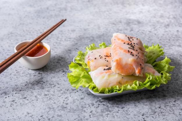 ベトナム料理の春巻き野菜、灰色の石の背景にライスペーパーのエビ。垂直フォーマット。アジア料理。