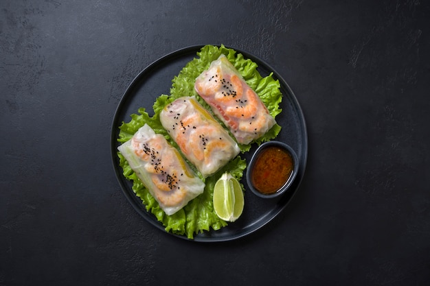 Vietnamese food spring rolls with vegetables, shrimps in rice paper on black. view from above. asian cuisine.