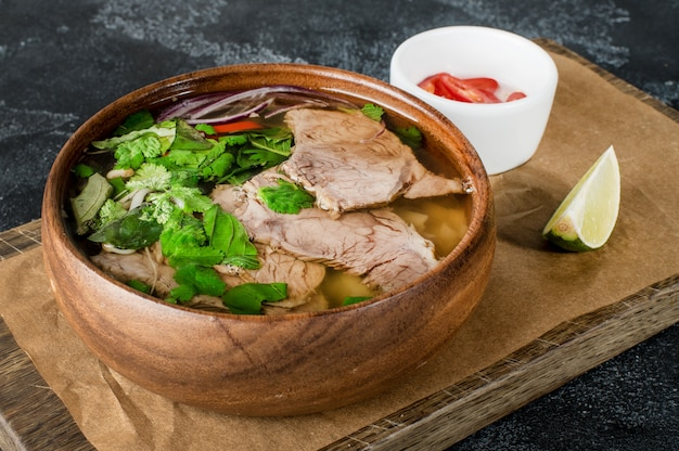 Vietnamese fresh rice noodle soup with beef, herbs and chili
