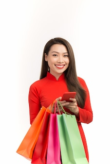 旧正月のオンライン ショッピングにスマートフォンを使用して伝統的なアオザイのドレスを着たベトナムの女の子