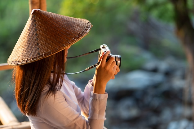 Vietnamese girl in traditional costume holding a film camera in the midst of nature