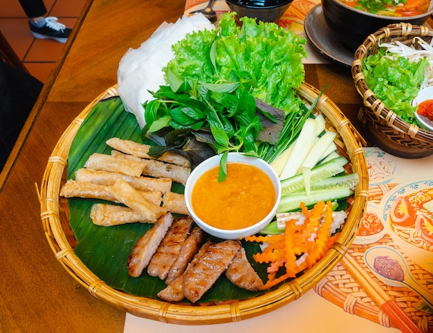 Vietnamese grilled meat or meatballs wrap set with vegetables and sweet sauce (nham neung) on table, local food