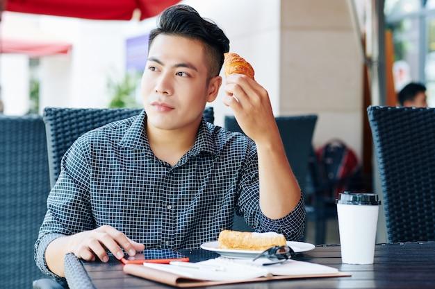 コーヒーとペストリーを楽しむベトナム人男性