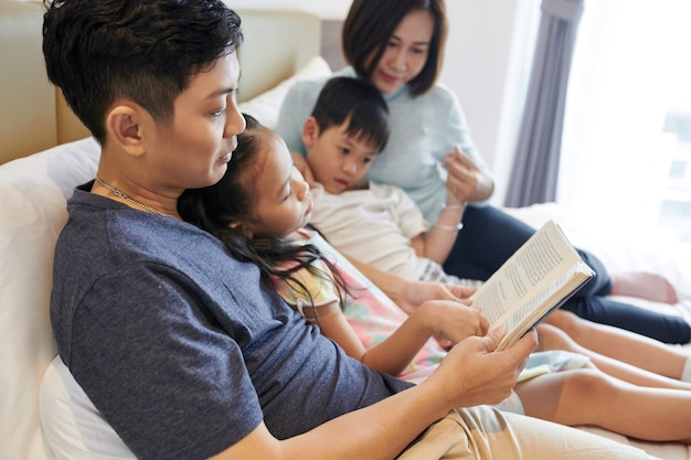 Vietnamese man reading interesting book for his children and wife whe they all are lying on bed