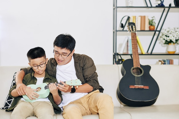 Vietnamese man teaching his talented preteen son playing ukulele at home