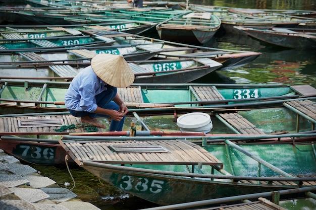 Вьетнамский мужчина в шляпе работает в лодке
