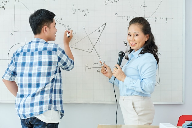 Vietnamese math teacher speaking in microphone and explaining new topic when student writing equation on whiteboard