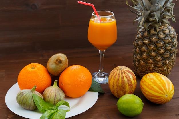 Вьетнамская дыня, лайм, инжир, апельсин, киви и ананас нагадятся на белой тарелке с деревянным фоном.