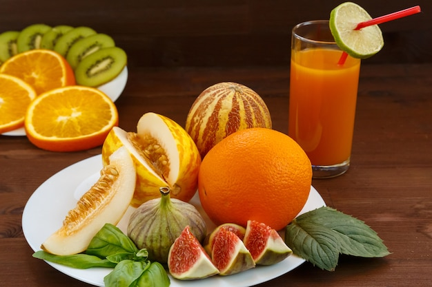 Vietnamese melon, lime, figs, orange, kiwi are on a white plate with a dull background