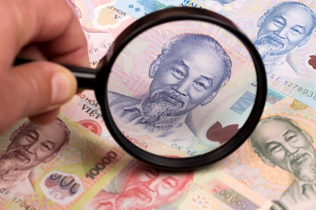 Vietnamese money in a magnifying glass a business background