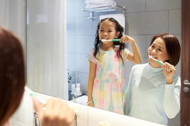 Вьетнамская мать и дочь вместе чистят зубы утром