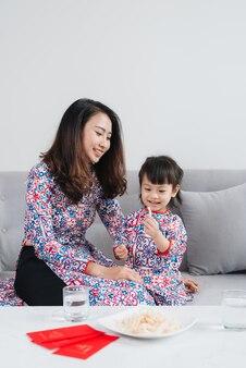 アオザイの伝統的な衣装を着たベトナム人の母と娘は、家で新年を祝います。テトホリデー。